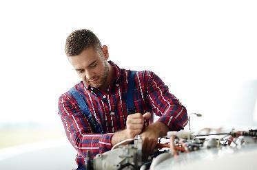 Afbeelding van man die onderhoud verricht aan een machine.